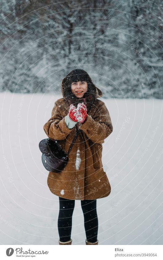 Eine Frau im Schnee Schneeball Winter lustig Freude dunkelhaarig Mensch weiß Winterlandschaft Landschaft draußen Natur schneien Schneefall Wintertag winterlich
