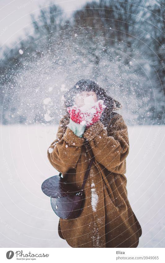Eine Frau mit einer Schneewolke vor dem Gesicht pusten winterlich Winter jung draußen schneien Schneegestöber Schneelandschaft Natur Winterstimmung Wintertag