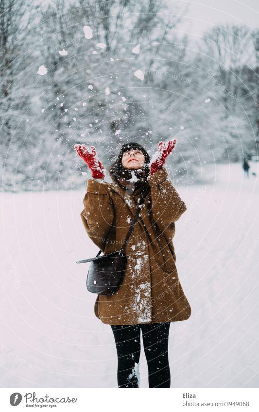 Frau wirft mit Schnee im Winter werfen Freude Schneelandschaft verschneit Natur draußen kalt weiß Winterstimmung Winterwald Wintertag Handschuhe Mantel jung