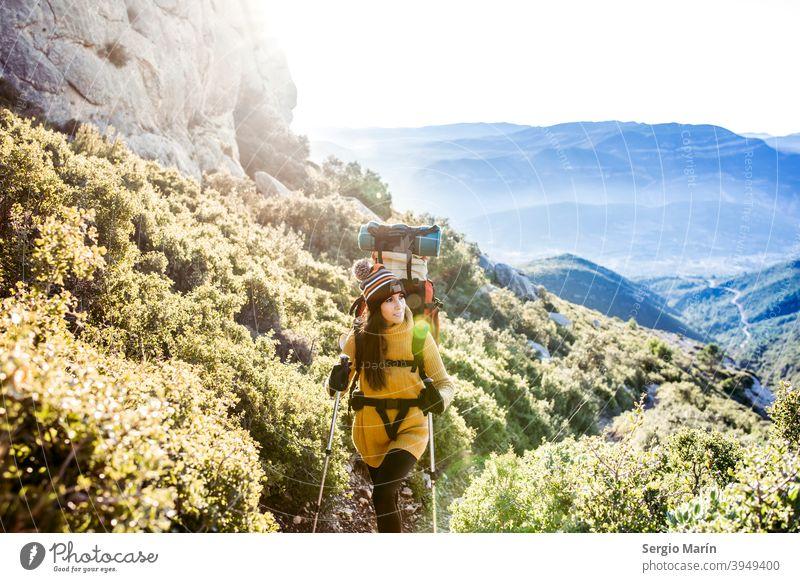 Happy Wandern Mädchen mit einem Rucksack steigt einen Bergpfad. Reisen Lifestyle-Konzept. Expedition Frau Camping Abenteuer Glück Trekking Entdecker im Freien