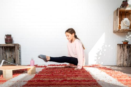 Mädchen, das Yoga zu Hause praktiziert. Konzept der Gesundheit. passen Training Übung Fitnessstudio Kind Tochter Pilates Sport Frau heimwärts Lächeln Glück