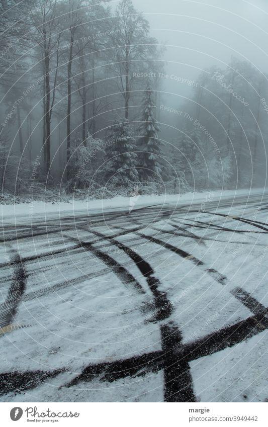 ein winterlicher Wald mit Reifenspuren auf einer glatten Straße mit Schnee und Eis Winter Glatteis Eis und Schnee Eis und Frost Spuren Bäume Natur Landschaft
