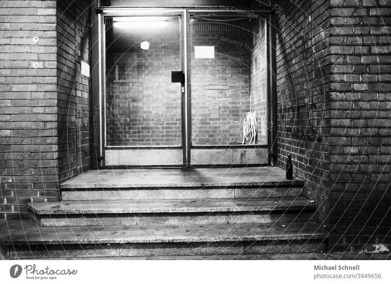 Eingangs-Glastür eines Backstein-Bürogebäudes mit einer Bierflasche davor Tür Eingangstür Menschenleer Außenaufnahme Haus Gebäude Mauer Treppe altmodisch