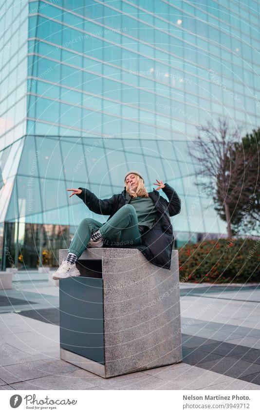 Blonde Frau in einem grünen Outfit, einer grauen Wollmütze und einer schwarzen Jacke mit einem Gebäude im Hintergrund Mode Porträt kalt anhaben niedlich