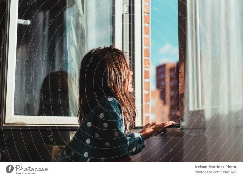 Schöne Aufnahme eines kleinen Mädchens mit dunklen Haaren, das an einem sonnigen Tag aus dem Fenster schaut. Sonne Sonnenlicht Porträt Kind Kindheit niedlich