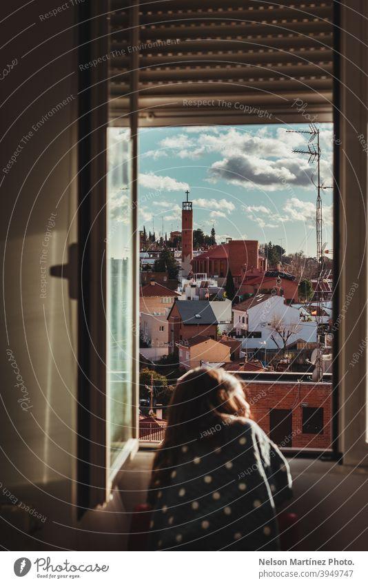 Schöne Aufnahme eines kleinen Mädchens mit dunklen Haaren, das an einem sonnigen Tag aus dem Fenster schaut. Porträt Kind Childhod heimwärts Viertel