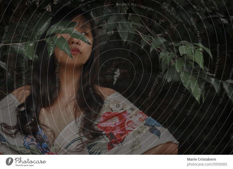 Schöne Frau in einem floralen Kleid unter dem dunklen tropischen Laub Sinnlichkeit Eleganz hübsch frisch Gesicht Blätter geheimnisvoll umgebungsbedingt Sommer