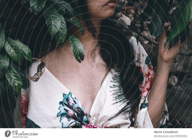 Porträt einer Frau im Blumenkleid gegen tropische Blätter Sommer geblümt Frühling im Freien feminin Stimmung rosa Zufriedenheit Jugend Frisur Sommerzeit