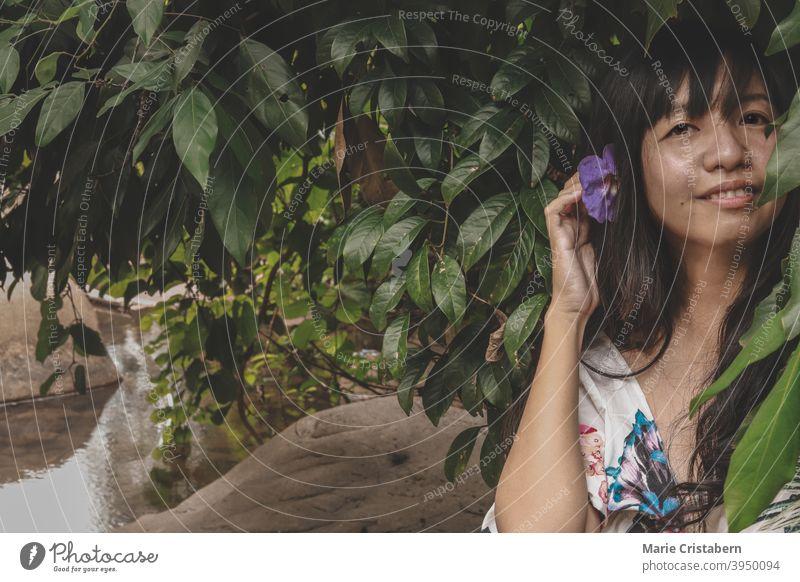 Schöne Frau mit Blume in ihrem Haar gegen die dunklen tropischen Laub zeigt Konzept der Frühling und Sommer im Freien Person genießen Spaß elegant lässig