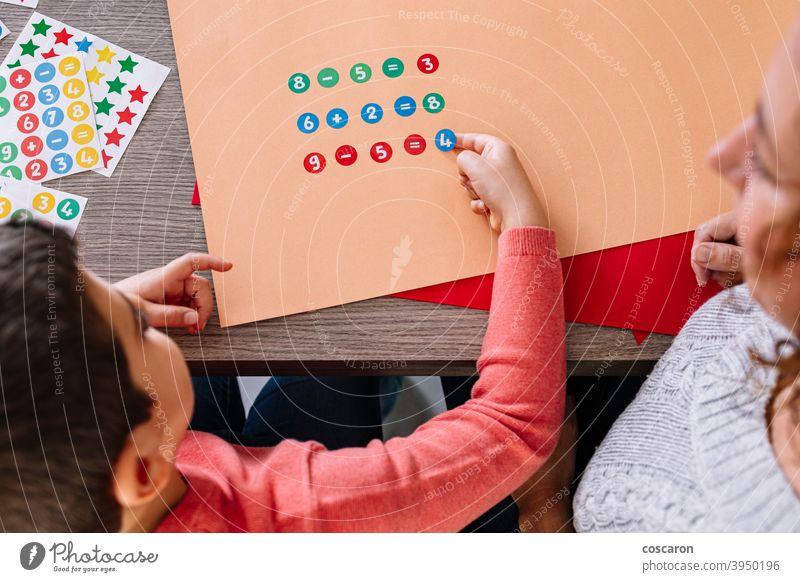 Mutter und Sohn machen Additionen und Subtraktionen mit Aufklebern zu Hause attraktiv Junge berechnend Kartenmaterial Kind Klassenraum farbenfroh Konzentration
