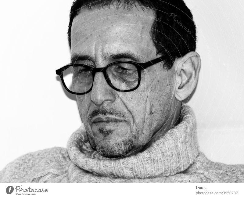 Ein lesender Mann Bart Falten Porträt Gesicht Brille sitzen Pullover Rollkragenpullover Blitzlicht
