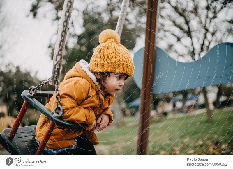 Kind spielt auf dem Spielplatz Spielplatzgeräte Sliden Winter Herbst orange Kinderspiel Kindheit Kindergarten Freizeit & Hobby Kleinkind Mensch Spielen Freude