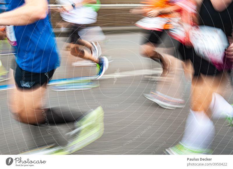 verwischte Marathonläufer auf einer Asphaltstraße Läufer joggingschuhe Jogging Geschwindigkeit Ausdauer Joggen rennen Jogger Bewegung Außenaufnahme Wettkampf