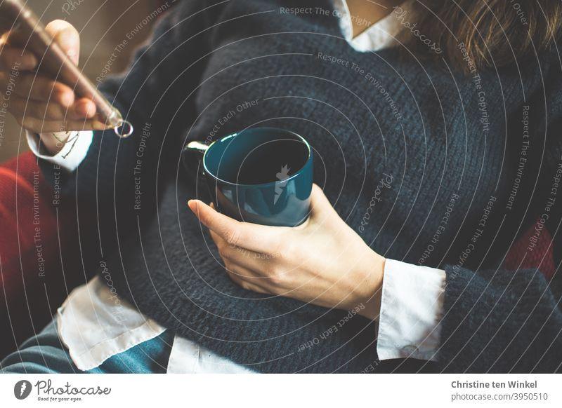 Die junge Frau im blauen Pullover sitzt gemütlich im Sessel und hält Kaffeebecher und Smartphone in ihren Händen. Oberkörper Portrait ohne Kopf Hand festhalten