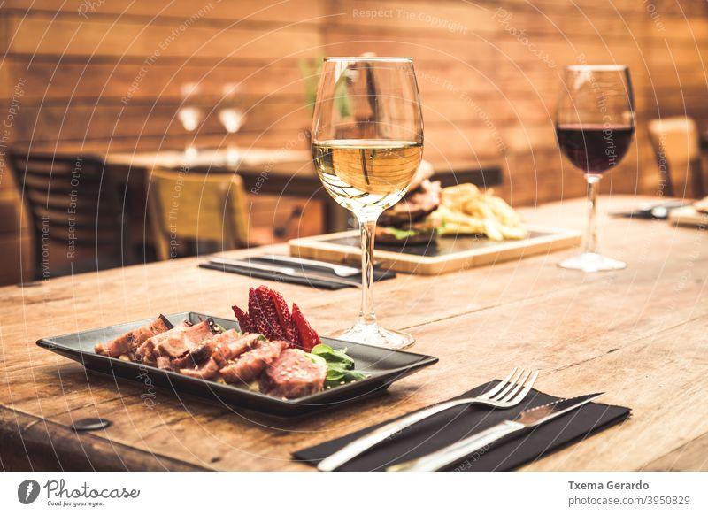 Traditionelle Restaurantatmosphäre mit Thunfisch-Tataki und Burger mit Pommes im Hintergrund auf rustikalem Holztisch und einem Glas Weißwein Fisch Chips