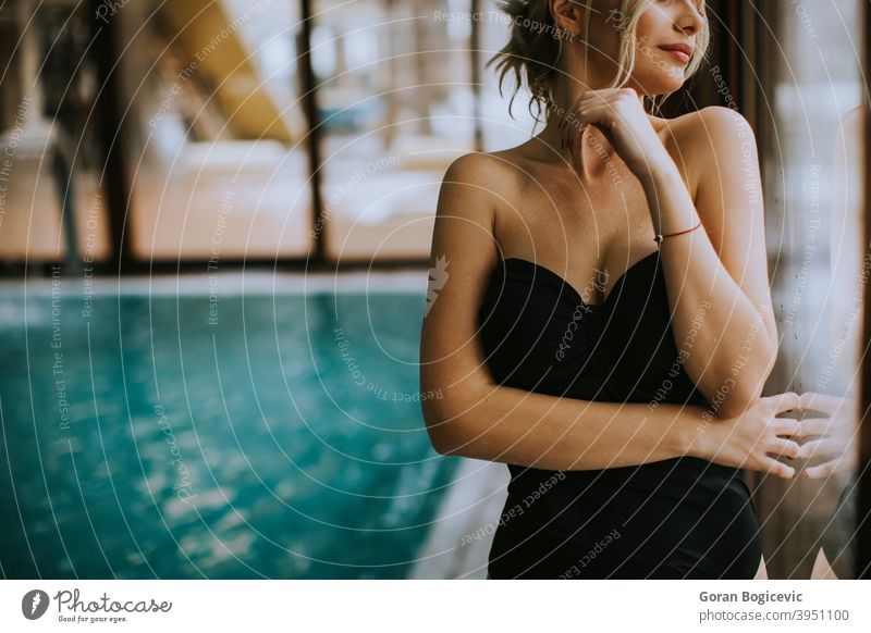 Schöne junge Frau steht am Fenster am Schwimmbad Erwachsener attraktiv schön Schönheit blau Körper Kaukasier niedlich Tag Fitness im Innenbereich Freizeit