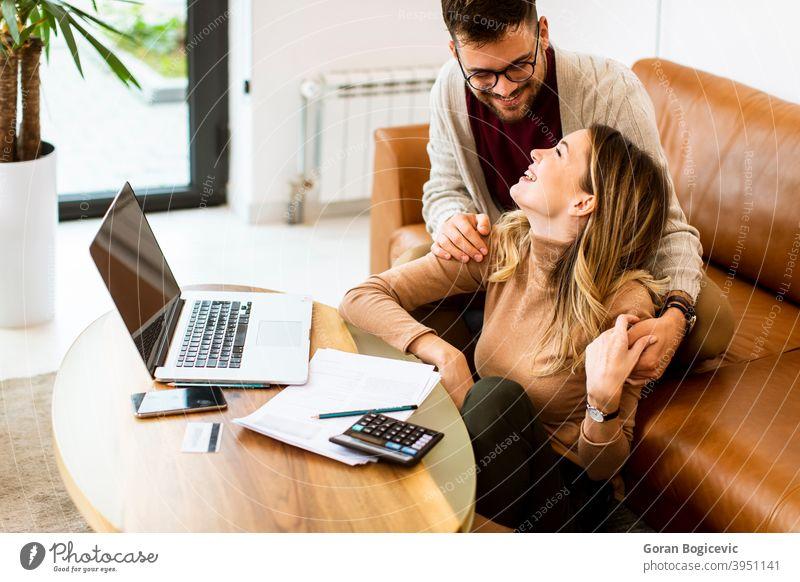 Junges Paar mit Laptop zusammen, während auf dem Sofa zu Hause sitzen Frau Mann Internet Glück Computer im Innenbereich Menschen heimwärts Kaukasier Liege Raum