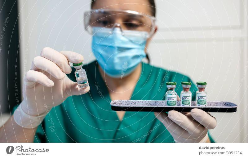Weiblicher Labortechniker bei der Untersuchung eines Fläschchens mit Coronavirus-Impfstoff. pharmazeutisches Labor Laborantin covid-19 Untersuchen Tablett