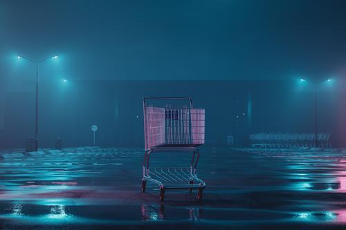 beleuchteter Einkaufswagen auf verlassenem, nebligem Parkplatz. Konzept Lockdown Tribüne im Freien Kaufhaus Kaufhof Gewerbe Straße wirtschaftlich parken Metall