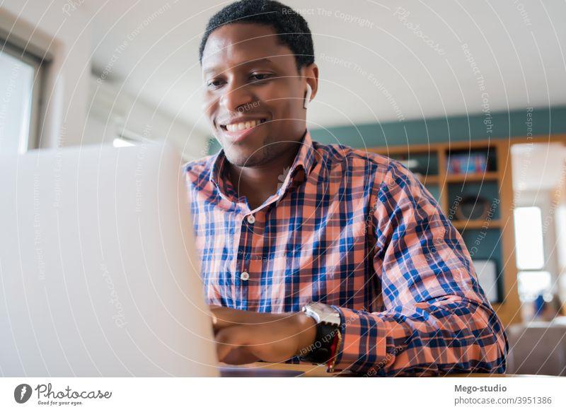 Mann bei einem Videoanruf von der Arbeit. heimwärts Büro Anruf Business Tagung Technik & Technologie Kopfhörer Laptop online Internet covid-19 schwarz Ohrhörer