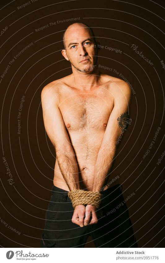 Mann mit Seil gefesselt stehend im Studio gebunden nackter Torso ohne Hemd Atelier Windstille ernst Figur sportlich männlich gutaussehend muskulös Körper Macho