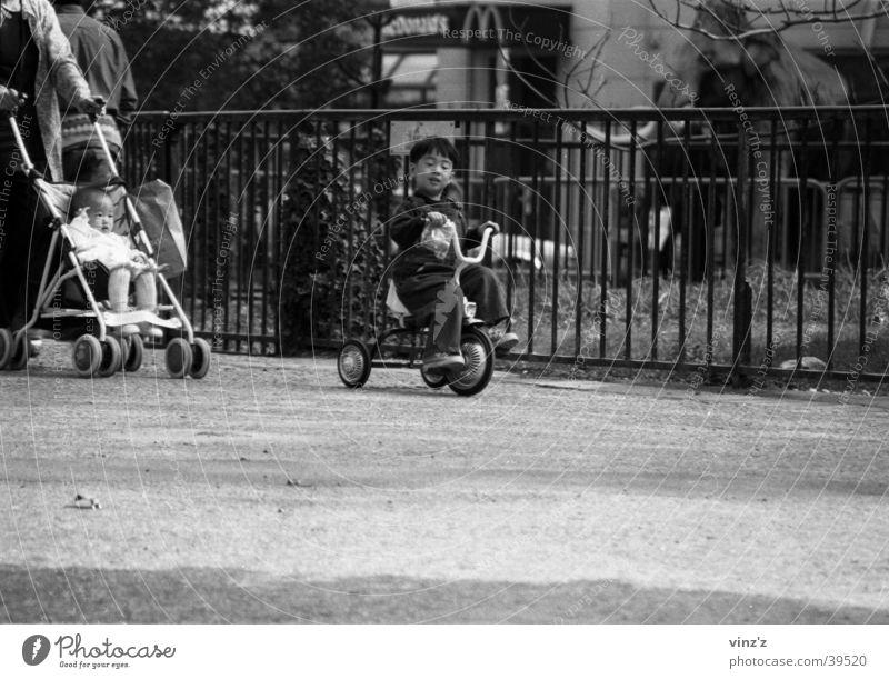 Dreirad im Jardin des Plantes Paris Kind Park Mann Schwarzweißfoto Asien