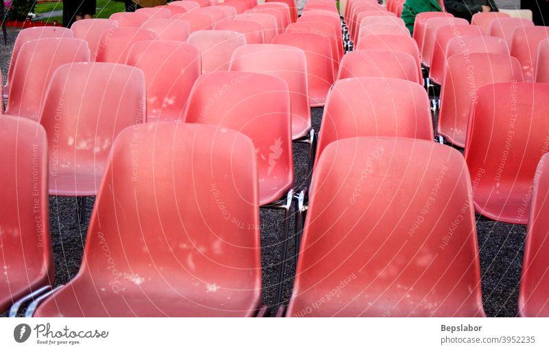 Rote alte Plastikstühle Reihe Sitz Stuhl Nahaufnahme Publikum Tagung Möbel Perspektive Sitzgelegenheit Zuschauerin leer Veranstaltung viele Öffentlich Linie