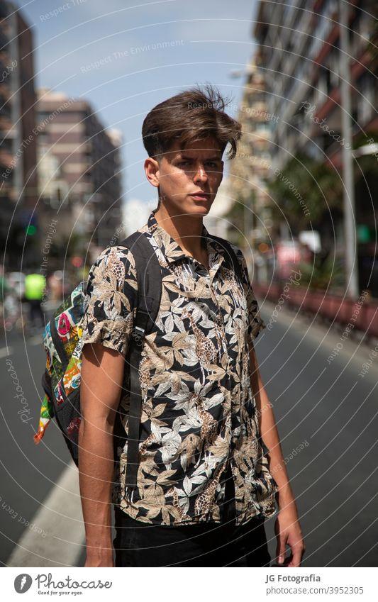 Porträt von authentischen jungen Mann mit Skateboard in der Mitte der Straße. Typ Skateboarderin urban Model retro Einstellung Aussehen Starrer Blick Gesicht