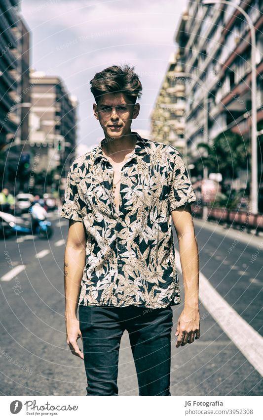 Junger Mann mit harter Kerl Gesicht zu Fuß in der Mitte der Straße. Porträt jung Typ Skateboarderin urban Model retro Einstellung Aussehen Starrer Blick Plakat