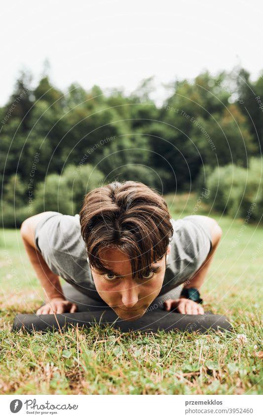 Junger Mann macht Liegestütze draußen auf Gras während seines Calisthenics-Trainings aktiv Aktivität Athlet sportlich Körper Bodybuilder Bodybuilding