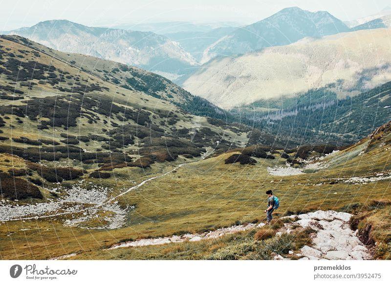 Junger Mann mit Rucksack Wandern in einem Gebirge, aktiv verbringen Sommerurlaub Aktivität Abenteuer Freiheit Gesundheit Freude Freizeit Natur Park Erholung