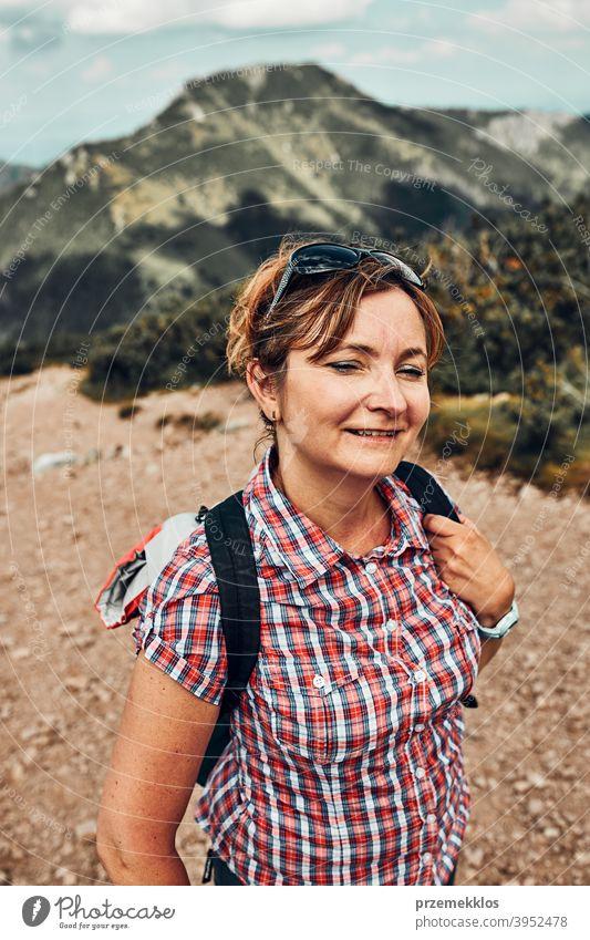 Lächelnde glückliche Frau mit Rucksack Wandern in einem Gebirge, aktiv verbringen Sommerurlaub Aktivität Abenteuer Freiheit Spaß grün Gesundheit Freude Freizeit