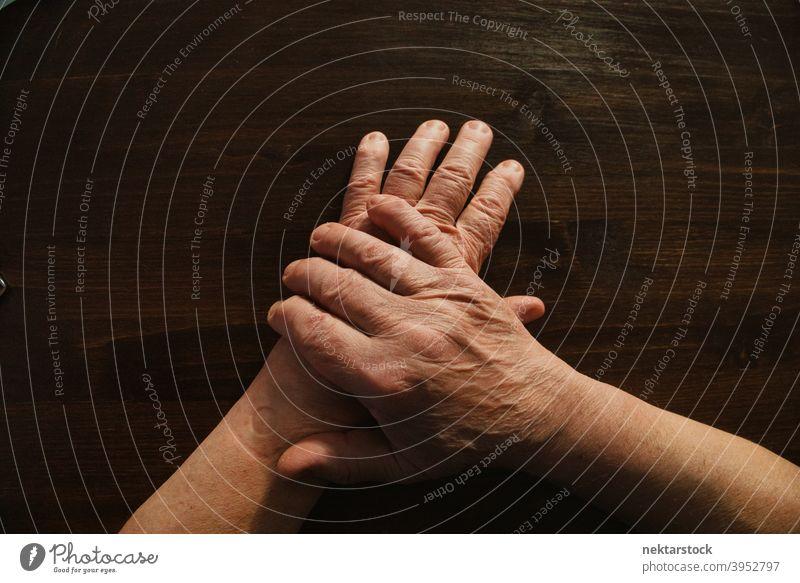 Hände und Arme eines alten Mannes auf einer hölzernen Oberfläche Hand Finger männlich Hochwinkelansicht nicht erkennbare Person Glied im Innenbereich