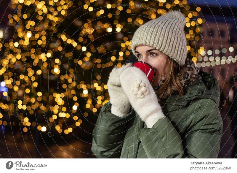 Trinkende Frau auf dem Weihnachtsmarkt Weihnachten Tasse trinken Markt Feiertag Glühwein Heißgetränk Winter im Freien Person Erwachsener Dezember Licht heiter