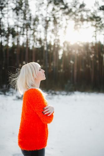 Niedliche Mädchen haben Spaß in der gefrorenen Park. Frau in einem gestrickten Pullover.die Hände des Mädchens gefroren Winter Porträt im Freien orange Natur