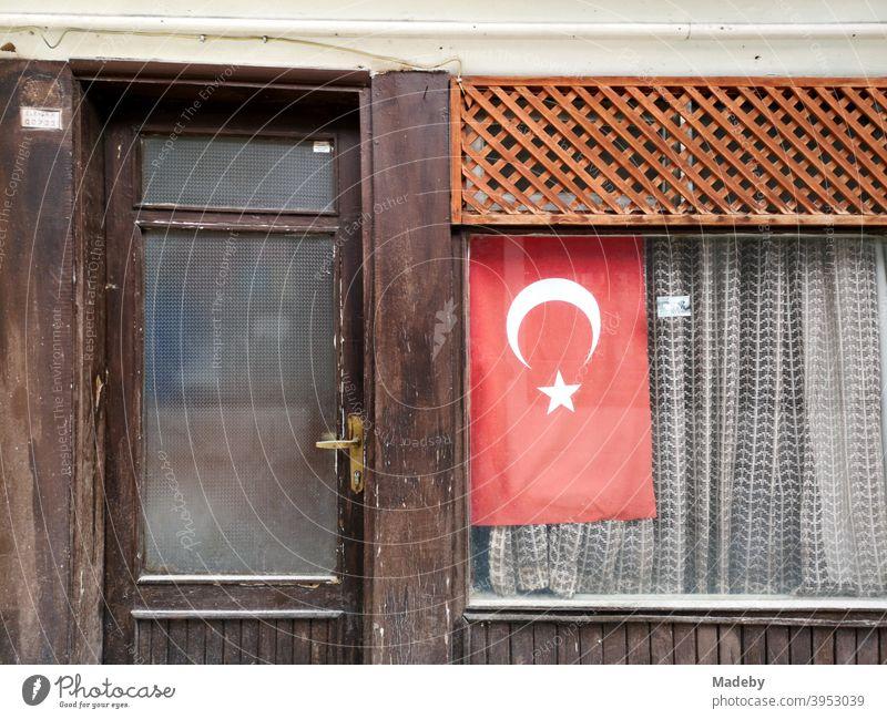 Die türkische Fahne im Schaufenster eines kleinen alten Geschäft mit Gardine in Göynük in der Provinz Bolu in der Türkei Flagge Nationalismus Nationalstolz