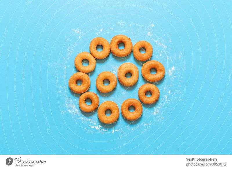 Donuts in einer Kreisform ausgerichtet. Hausgemachte frische Krapfen, Ansicht von oben Amerikaner gebacken Bäckerei Blauer Hintergrund Frühstück Kuchen Kalorien
