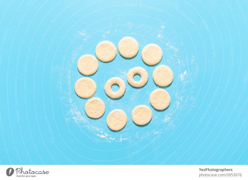 Herstellung von Donuts flachlegen. Ungekochter roher Teig für Donuts vorbereitet ausgerichtet Amerikaner backen Blauer Hintergrund Frühstück Kuchen Kalorien