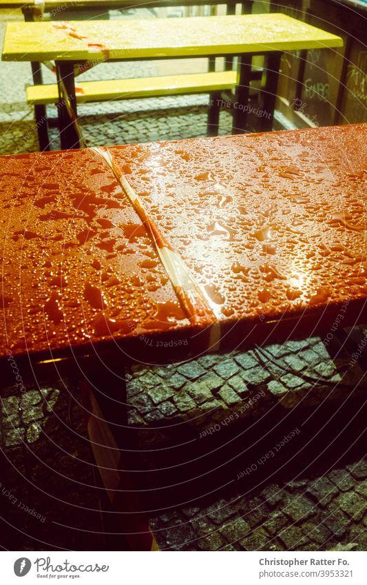 Abgesperrte Sitzgruppe in Berlin während des zweiten Lockdown in der Corona Pandemie Regen Licht Nacht ungemütlich kalt nass gelb Nachtaufnahme Winter