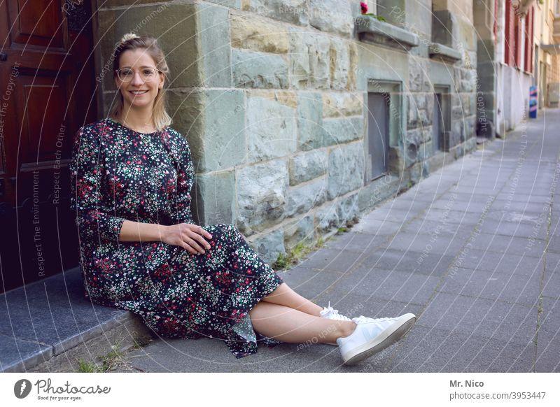 junge Frau sitzt vor der Haustüre und wartet sitzen Tür warten Fassade Gebäude Altstadt Eingangstür Hauseingang Sommerkleid Bürgersteig Verabredung Mode Porträt