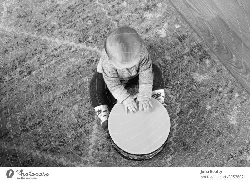 6 Monate altes Baby spielt Trommel, während es auf einem Teppich auf dem Boden sitzt; Schwarz-Weiß-Bild aus der Vogelperspektive Bodentrommel Hände schlagen