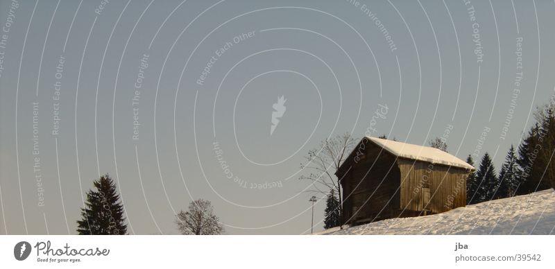 Scheune vor Himmel blau Schnee Baumkrone