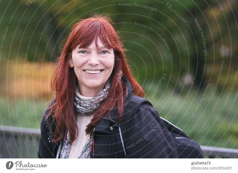 Glückliche, lächelnde Frau mit roten langen Haaren draussen in der Natur Blick in die Kamera Vorderansicht Oberkörper Porträt Zentralperspektive