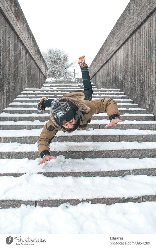 Mann rutscht auf Eis aus und fällt die Treppe hinunter Rutschgefahr Ausrutschen und Sturz Ausrutschen auf Eis rutschig ausrutschen herunterfallend