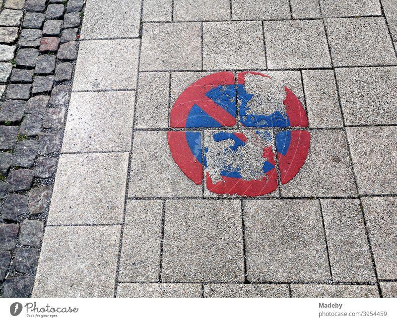 Vergilbtes und zerbröselndes aufgemaltes Verkehrszeichen im Halteverbot auf dem grau gepflasterten Bürgersteig neben der Fahrbahn aus traditionellem Kopfsteinpflaster in einer Kleinstadt