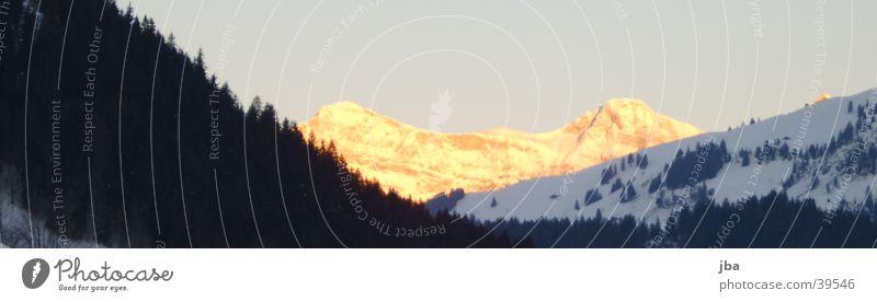 Sonnenaufgang über Saanen Sonne dunkel Schnee Berge u. Gebirge hell Gstaad