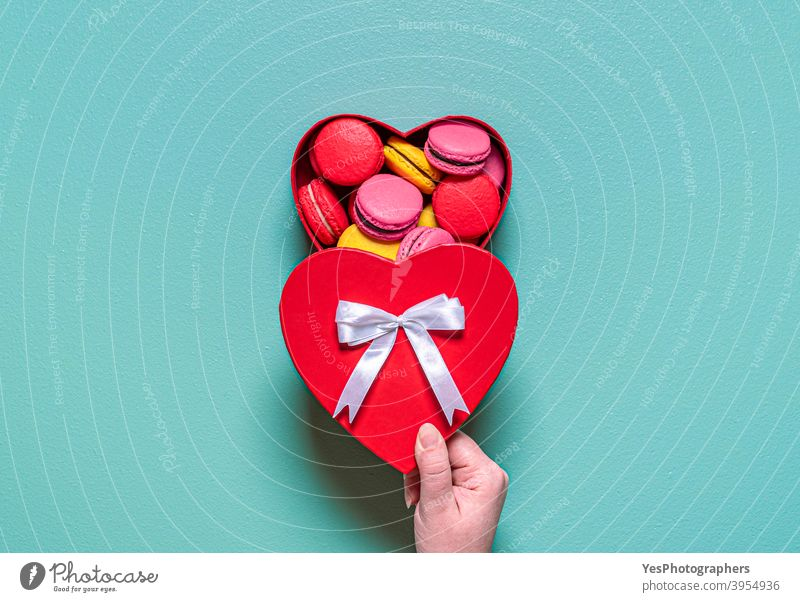 Macarons in einer Geschenkbox. Frau Hand öffnen Box mit Macarons. obere Ansicht Mandelplätzchen Handwerklich Hintergrund gebacken Kasten Schokoladenganache