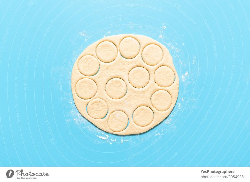 Herstellung von Donuts Prozess. Handgemachter Donut-Teig in runde Formen geschnitten ausgerichtet Amerikaner backen Blauer Hintergrund Frühstück Kuchen Kalorien