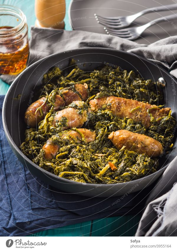 Italienische Würstchen mit Rapini-Brokkoli in der Pfanne Wurstwaren Fleisch rapini Kale schwarz Sekunde Speise Abendessen Mittagessen Mahlzeit dienen Tisch