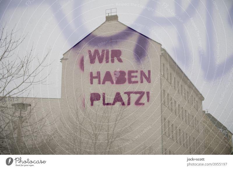 WIR HABEN PLATZ in der Stadt Brandmauer Architektur Stadthaus Fassade Straßenkunst Doppelbelichtung Großbuchstabe Wort Kreativität Äste Winter Subkultur